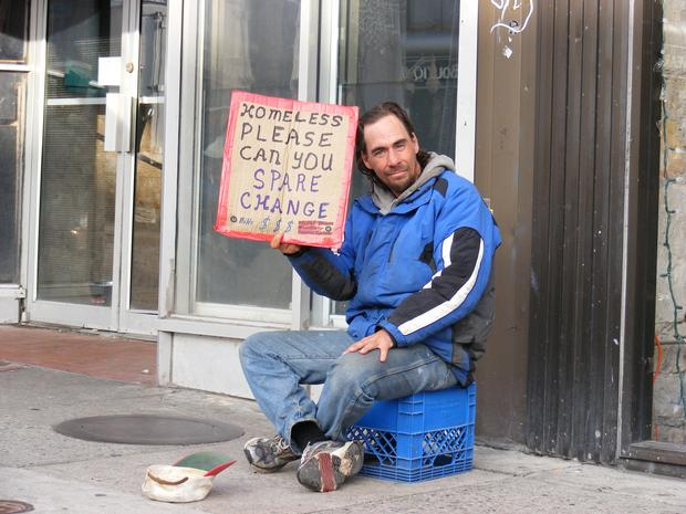 A homeless man appeals to passersby for help in Guelph.