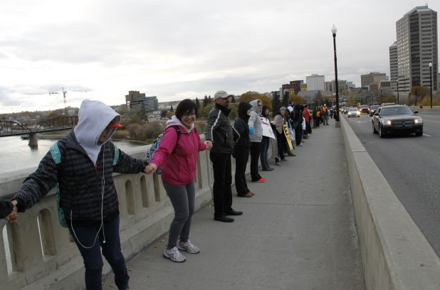 A human chain spans a bridge during an anti-poverty protes in Saskatoon.
