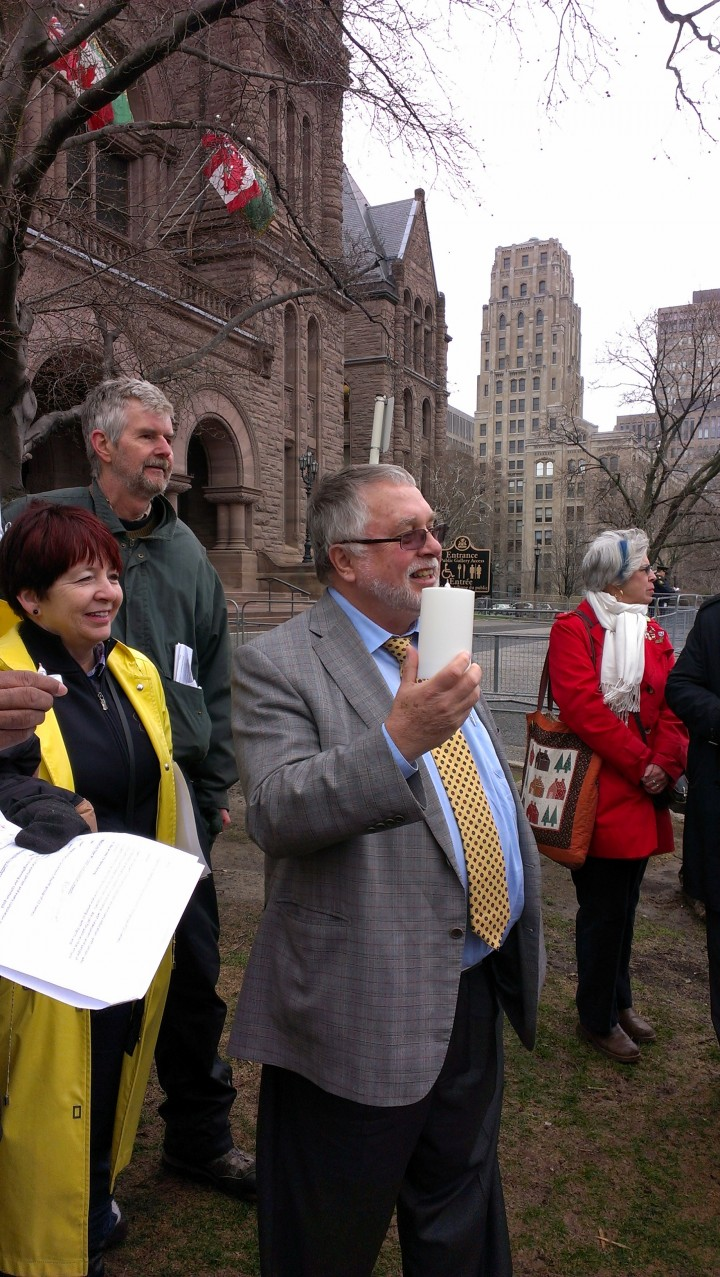 Hon. Ted McMeekin holds a candle at ISARC Interfaith Prayer Vigil, April 30, 2014