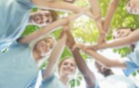 Support concept. Happy volunteers holding hands in circle and smiling, teambuilding exercise, teamwork and help, view from below, copy space