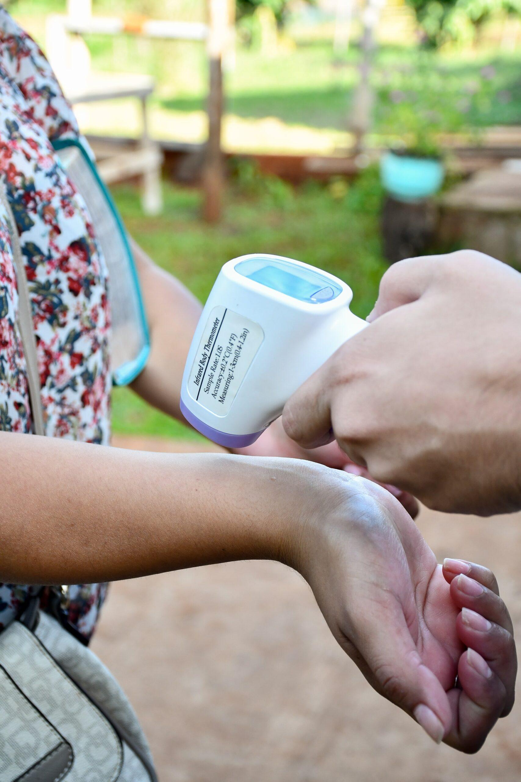 Person taking someone's temperature on wrist